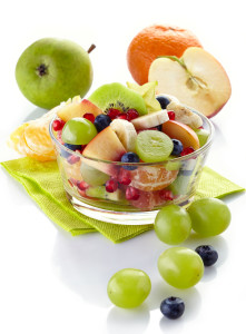 Bowl of fresh healthy fruit salad on white background