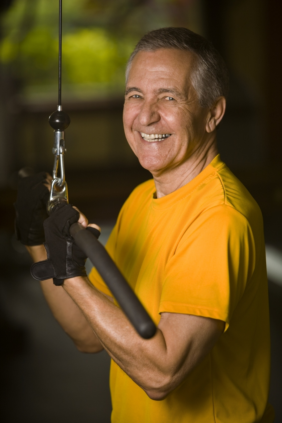 Happy senior man performing a reverse tricep extension on a lat pulldown machine in the gym.